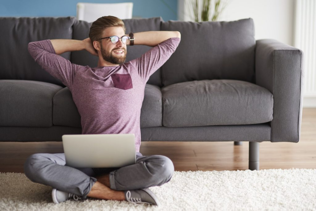 Young Man Working from home sitting on floor hands behind head stretching
