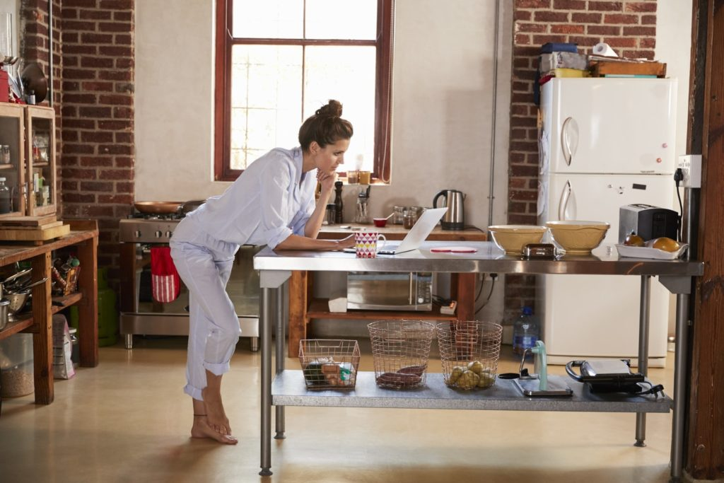 Woman working form home leaning on kitchen island